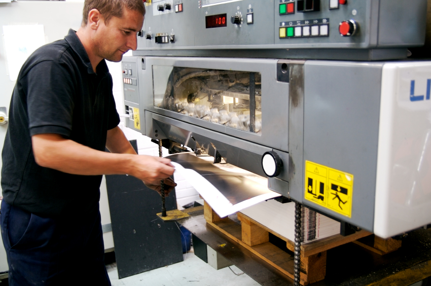 A printer pulling a sheet from a lithographic printing press...